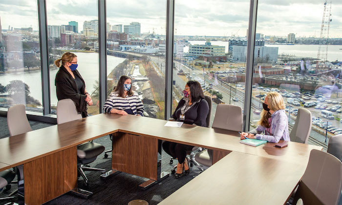 Co-workers meet in a conference room on a top floor of Waitzer Hall. A dramatic view of downtown Norfolk and the surrounding waterfront is visible behind them.