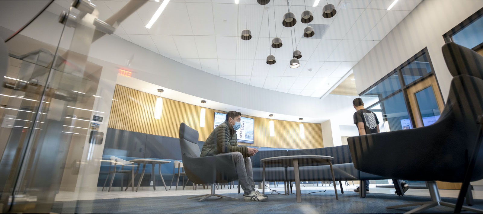 One of several lobby areas in Waitzer Hall furnished with modern tables and chairs; and outfitted with wood paneling, wall sconces and overhead light fixtures. Lobby areas in the education podium provide space for students to mix (post-COVID-19), study or relax.