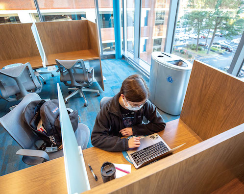 Two students wearing masks talk before the beginning of an exam in the test center in Waitzer Hall. A plastic barrier separates each workstation.
