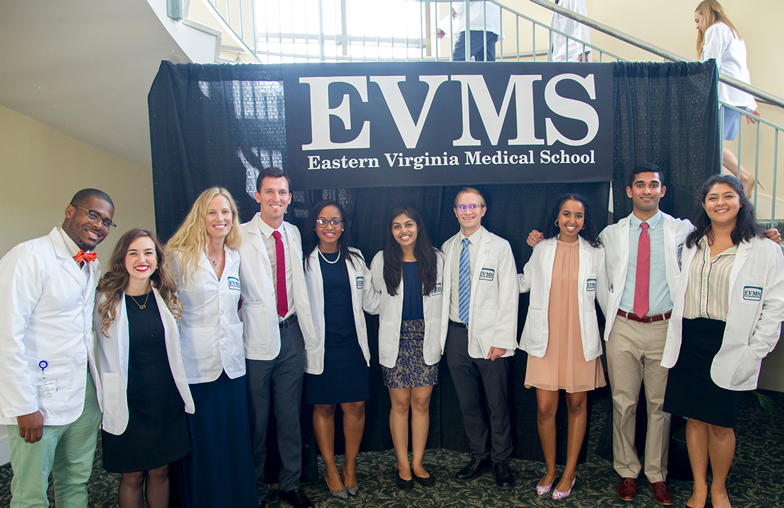 A group of male and female EVMS students of several ethnicities wearing white coats and standing in front of an EVMS Banner