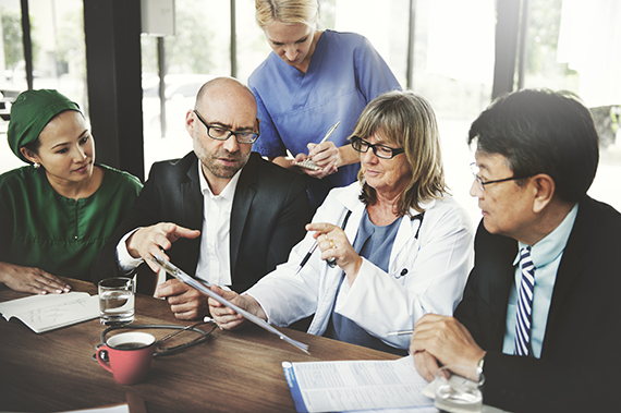 Five medical professionals talk together during a meeting.