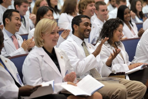 A diverse group of medicals students smiling and clapping in an academic auditorium.