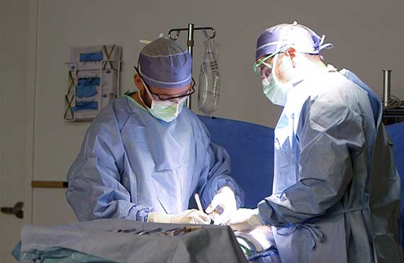 Surgical Assisting students in masks practice surgical tasks in an OR setting
