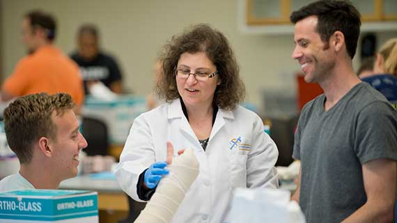 An instructor works with two PA students as they practice splinting.