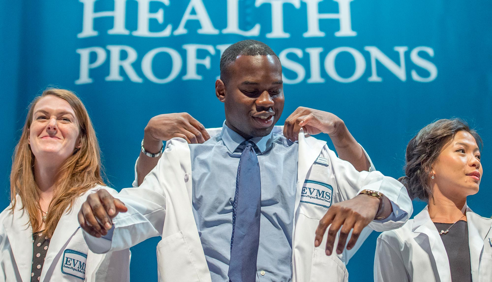 A PA student puts on his white coat during the PA White Coat Ceremony, signifying his transition from student to practitioner.