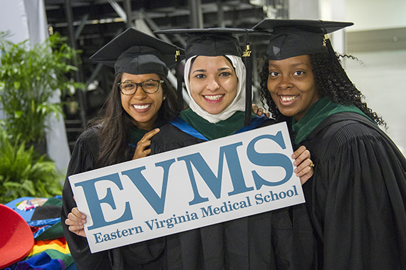 Three MD students wearing graduation robes pose for a picture with a sign depicting the EVMS logo.