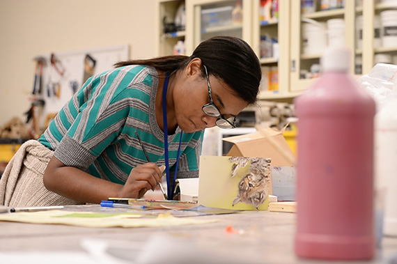 An Art Therapy students creates artwork in the classroom.
