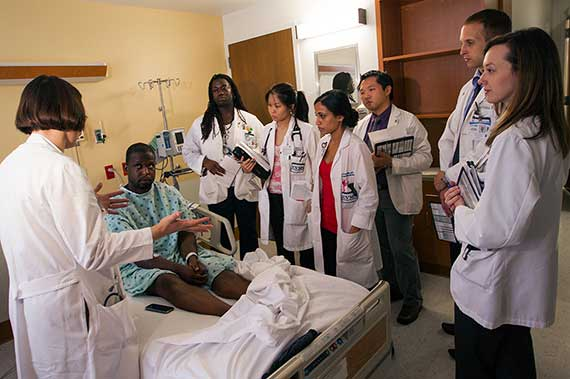 A team of residents visits with a patient
