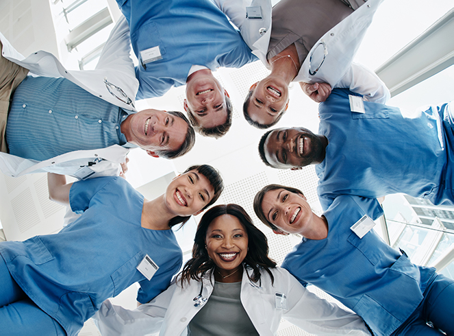 Health care workers standing in a circle with their arms around each other