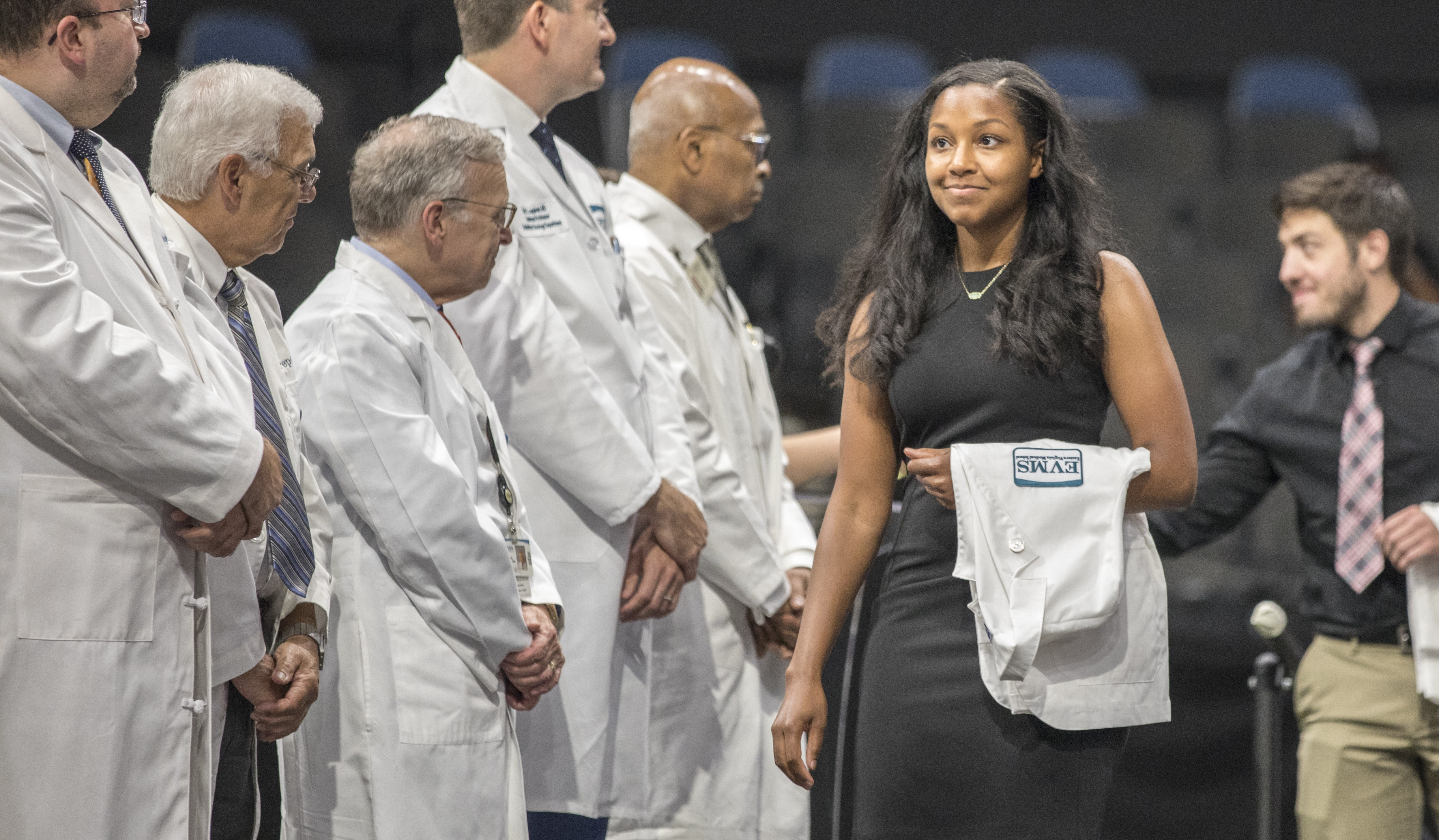 An EMVS student looks proud while walking across the stage during the 2019 MD White Coat Ceremony