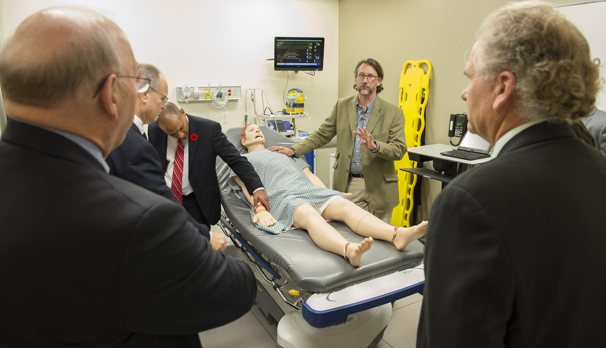 Faculty and staff surround a training manikin in the Sentara Center for Simulation and Immersive Learning at EVMS.