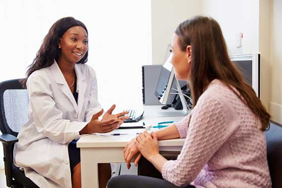 A physician talks with a clinical trial participant.
