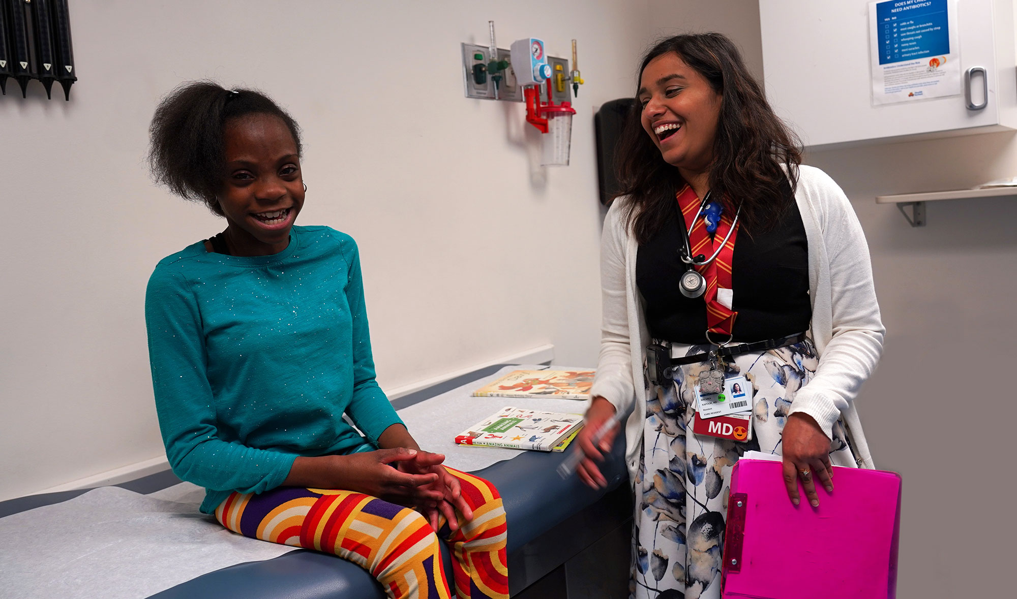 Dr. Kapoor laughs with a young girl, who is smiling while waiting for her checkup, in an exam room.