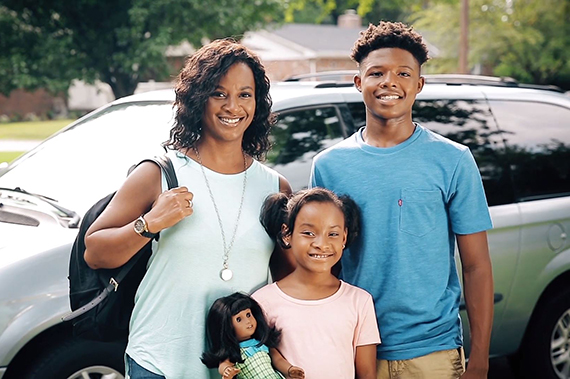 A family poses in front of a vehicle.