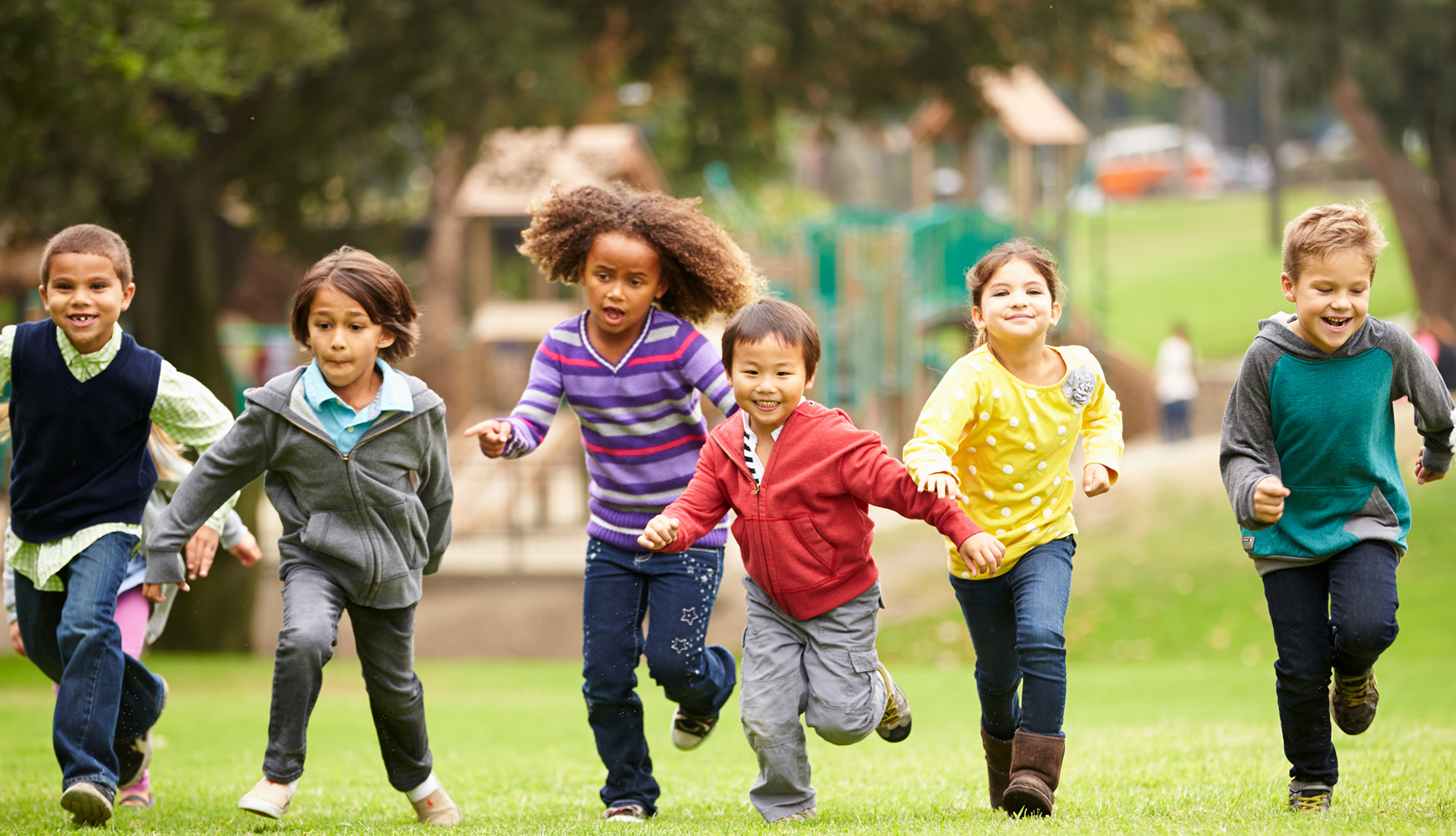 Several children run together in the park.