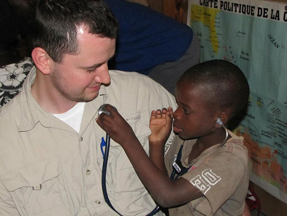A child listens to a fellow's heartbeat through a stethoscope in Haiti.