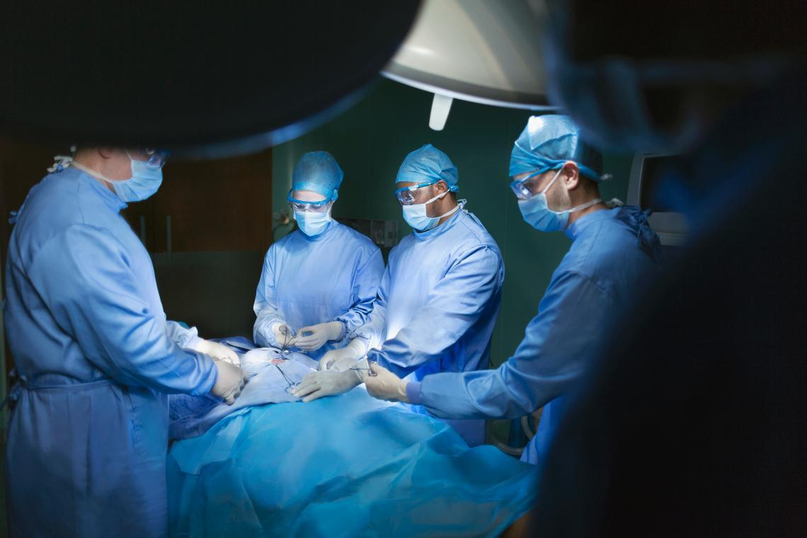 Image of surgeons performing a procedure in an operating room.