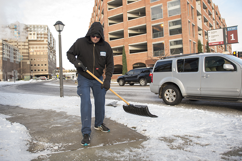 Maintenance Engineer Dwayne Gibboney shovels snow and ice from a sidewalk Tuesday morning, Jan. 10. Mr. Gibboney and many of his colleagues spent much of the weekend clearing roads and sidewalks within the medical center. EVMS will be open normal hours beginning Wednesday, Jan. 11.