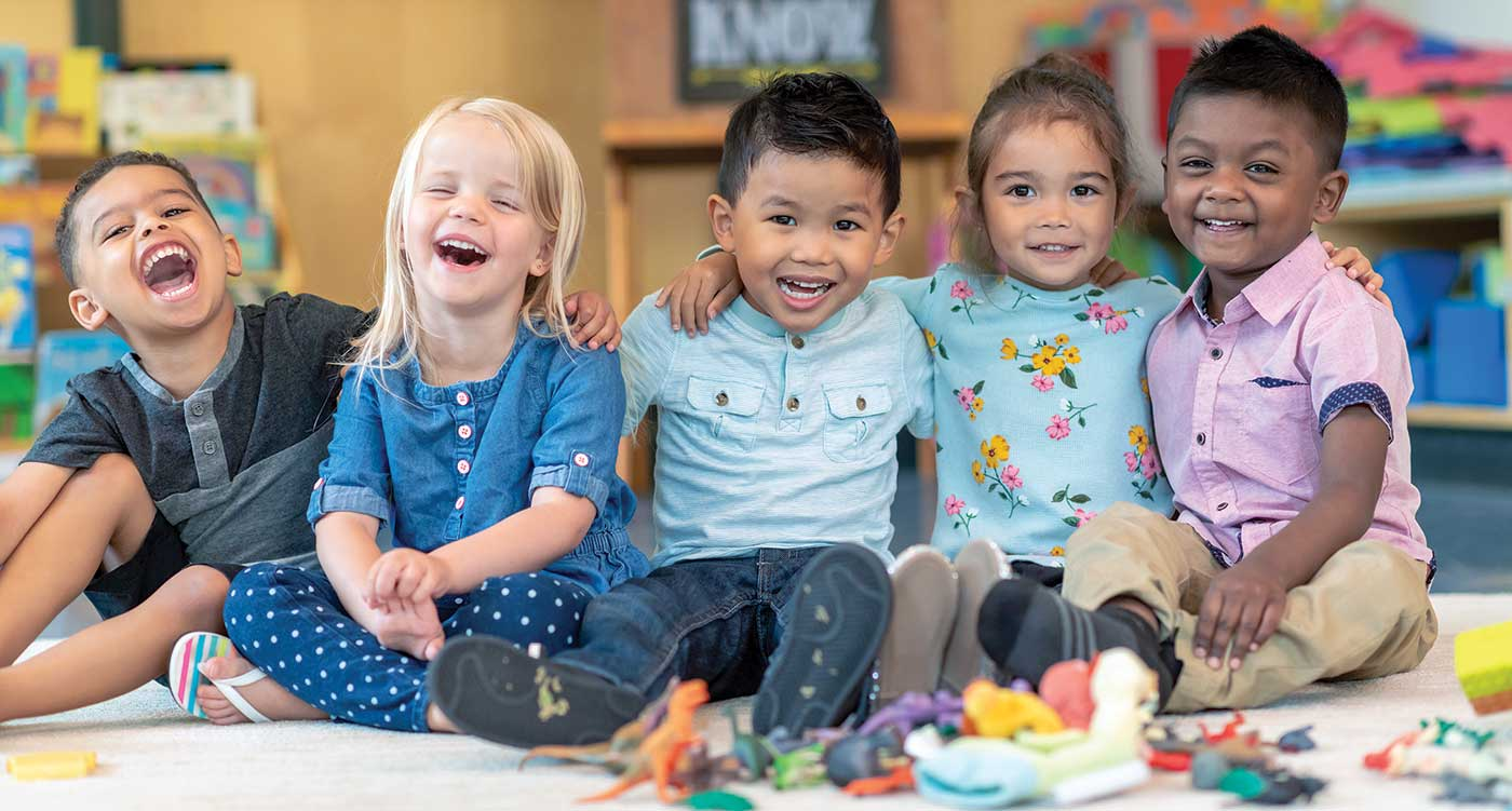 Toddlers in a classroom laughing and smiling