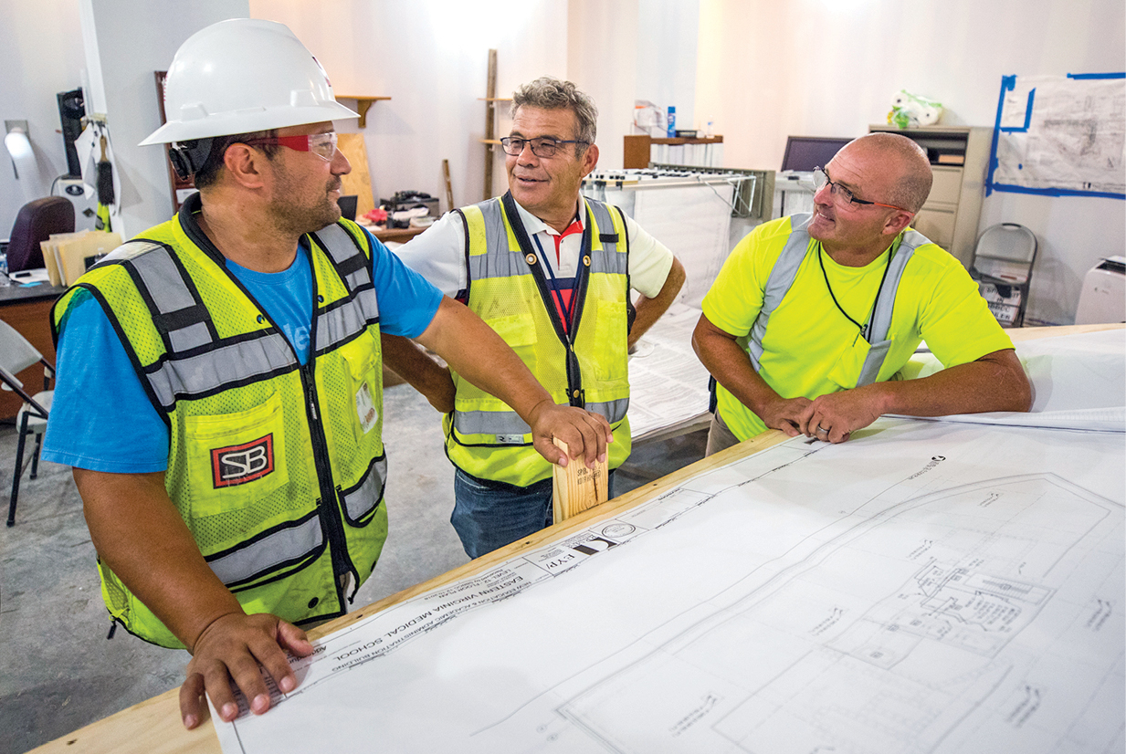 Greg Vuyovich, Project Manager for EVMS, center, speaks with Carleton Bitgood, S.B. Ballard EVMS Project Manager, left, and Billy Hubbard, S.B. Ballard EVMS Superintendent.