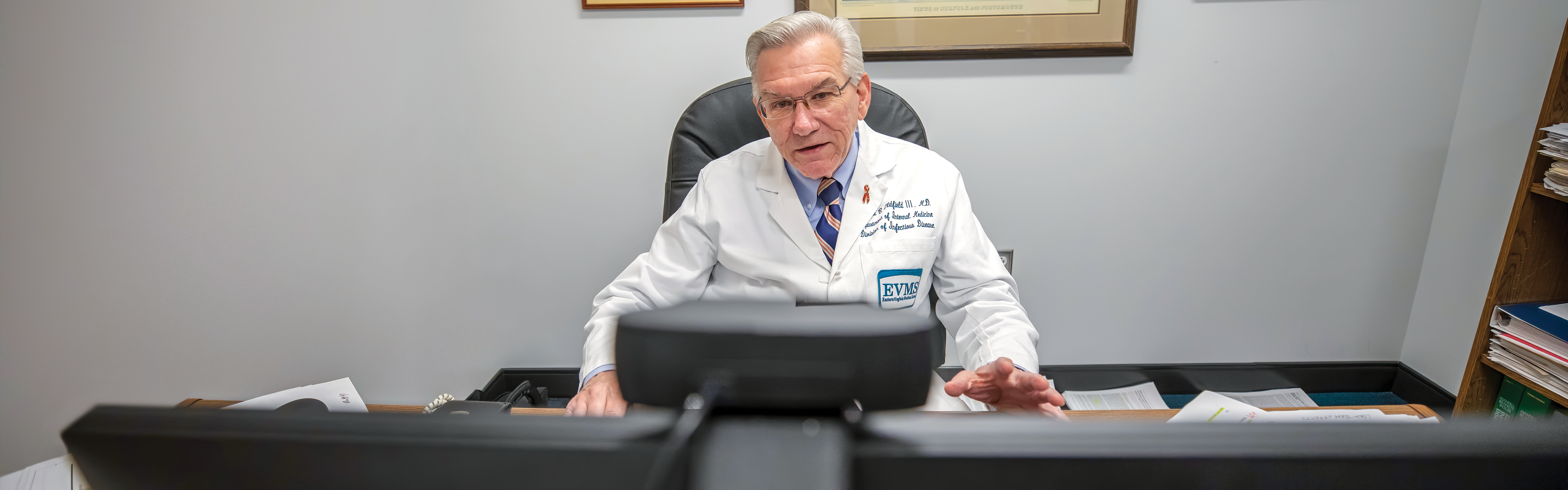 •Dr. Edward Oldfield sits in front of his computer at his office desk while on a video conference call. There is a web cam attached to the top of his computer monitor.