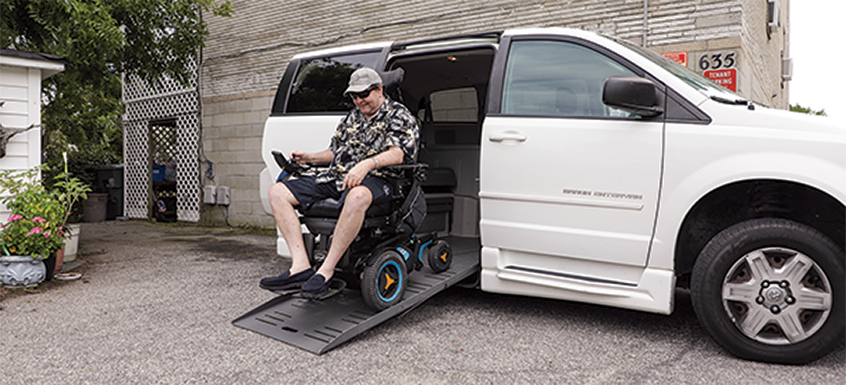 Eddie using his wheel chair to exit off of a ramp from the side of his specially equipped van.