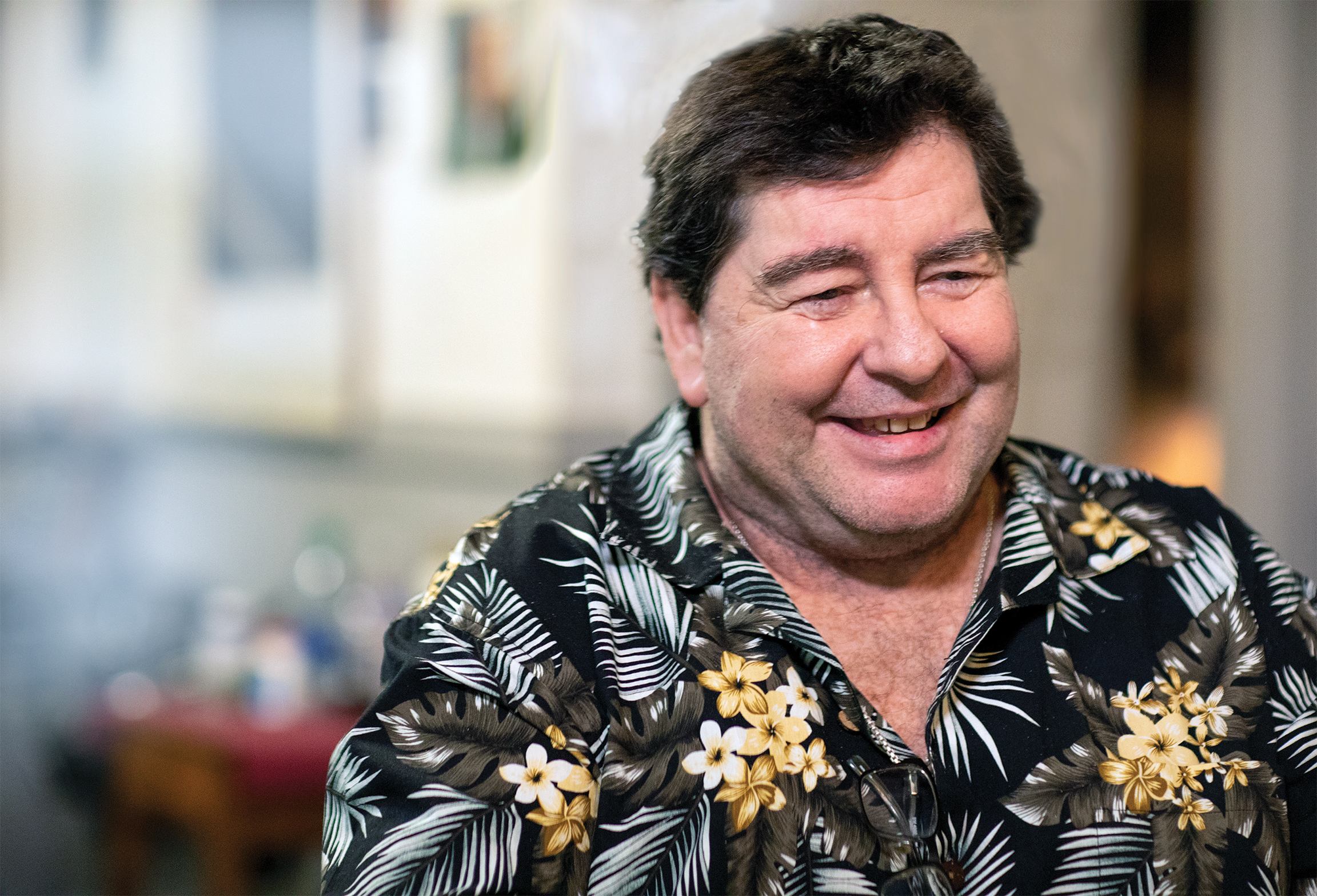 A smiling Eddie Roebuck wearing a tropical print shirt looks away from the camera.