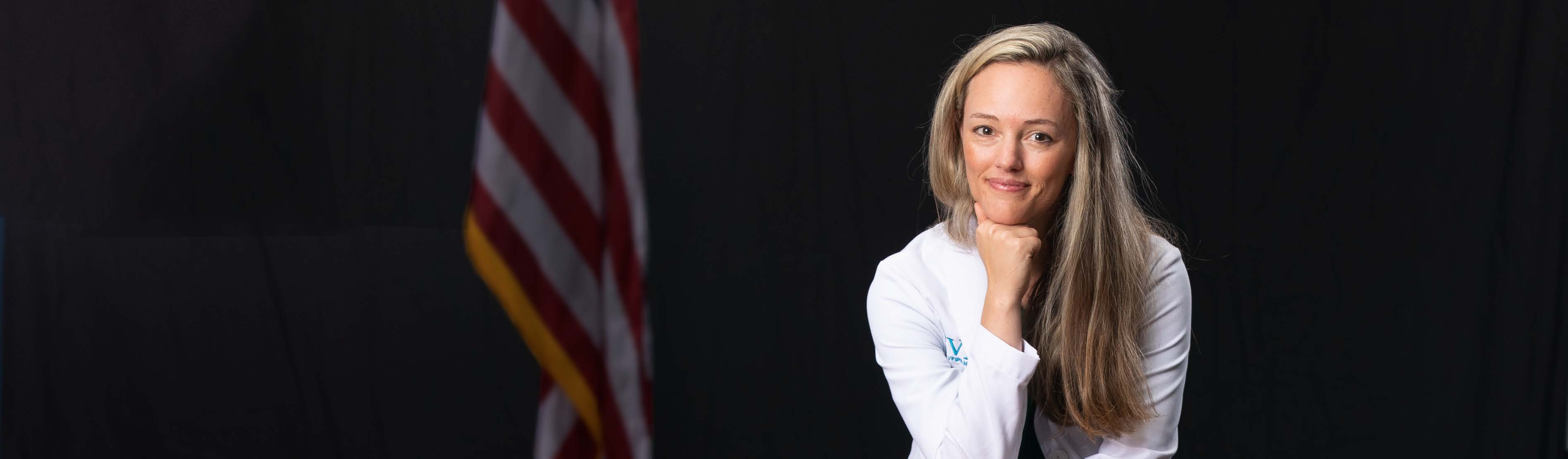 Dr. Brooke Hooper smiles at the camera and stands confidently in her white coat with the American flag out of focus behind her.