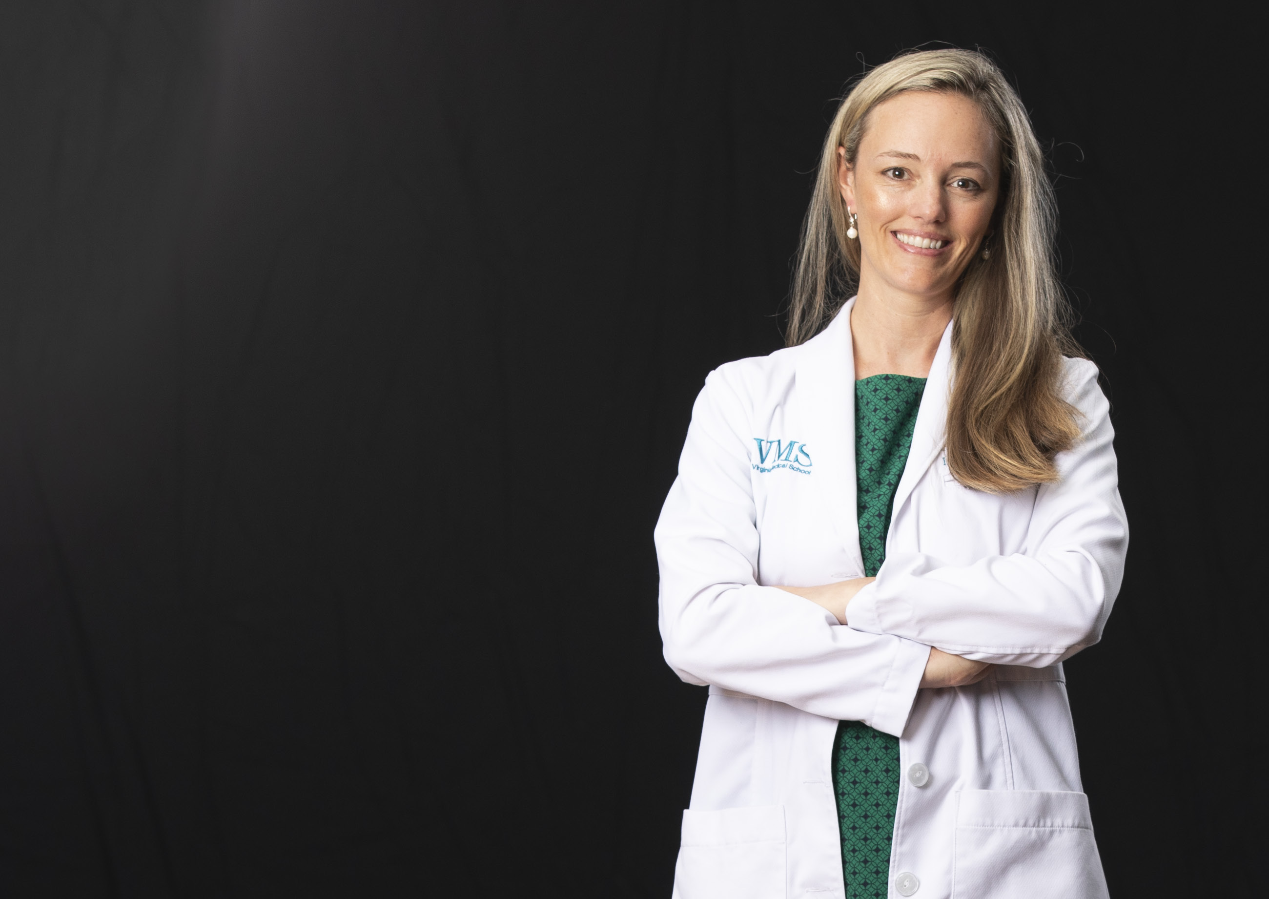 Dr. Brooke Hooper sits with her chin resting on her right hand and her legs crossed at the knees.