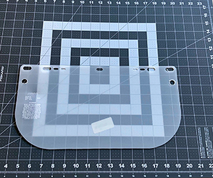Align plastic shield in middle of mat; the opaque plastic is on the inside of the shield – you can tell by the engraving on the side.