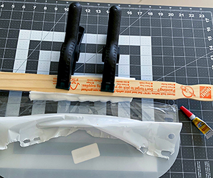 Center and glue the foam to the inside of the shield (opaque plastic side) using superglue. Use clamps to apply pressure for about 10 minutes.