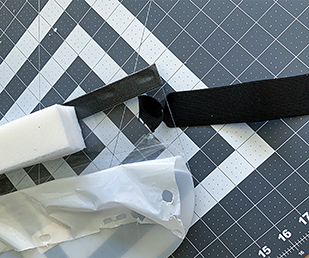 Attach a 15.5 inch piece of high-strength (2 inch) elastic to the shield. Insert elastic from outside in through the side hole as shown – for no more than 2 inches. Repeat on the other side as shown.