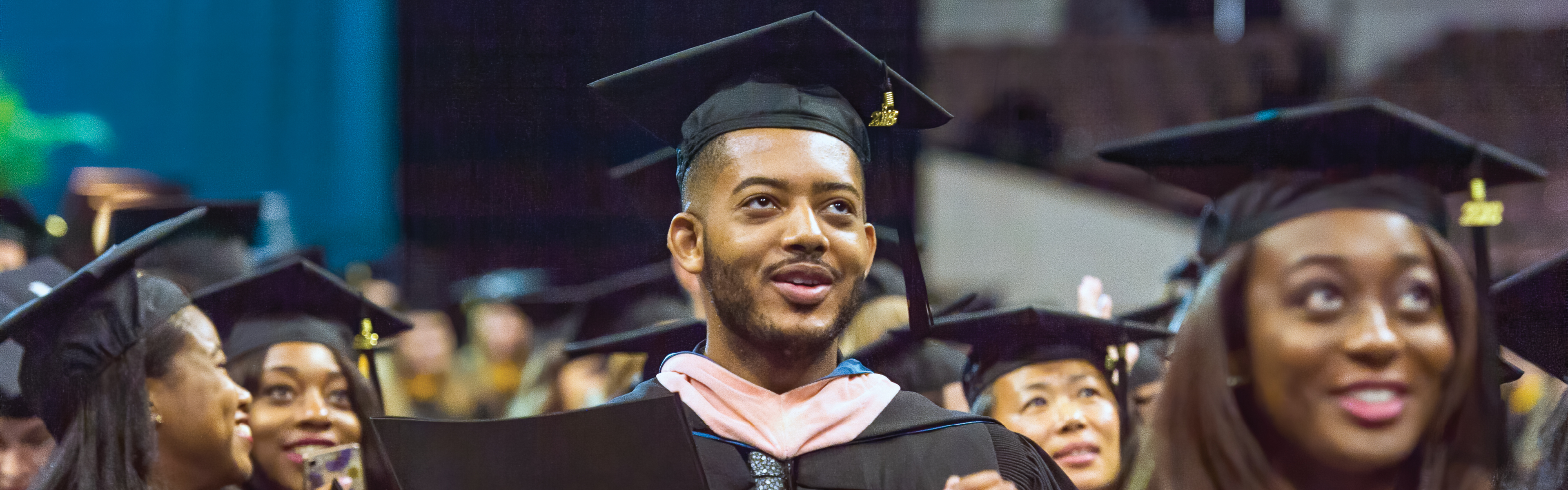 A group of diverse students at an EVMS Commencement ceremony. The figure in focus is a Black male graduate in cap and gown with a hopeful expression.