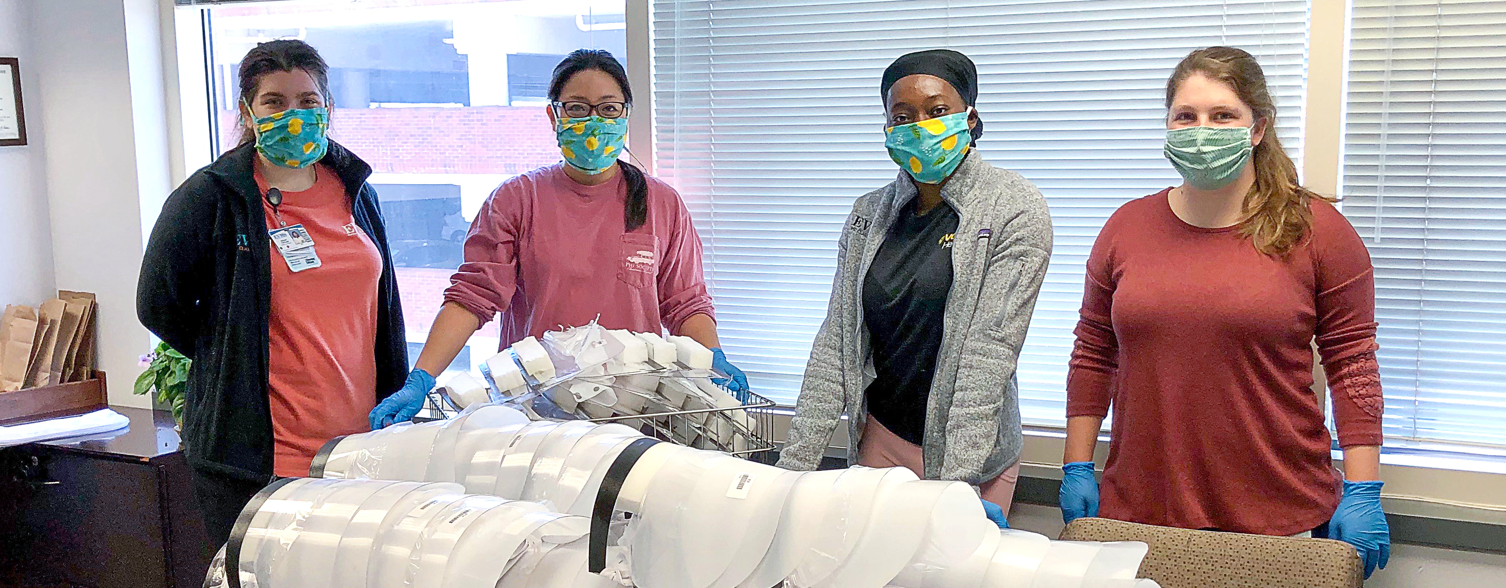 Four young women stand behind a desk covered in assembled face shields and face shield parts.