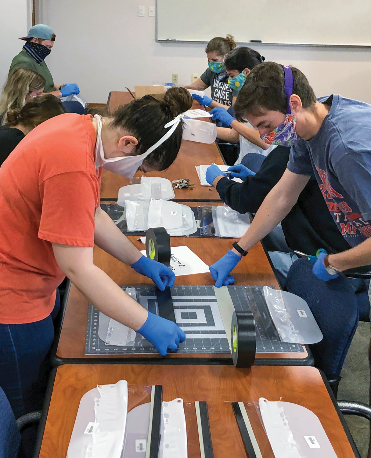 A female and male student in the foreground wear face covering and protective gloves as they use duct tape to cover the holes on the plastic coverings used to make the face shields.