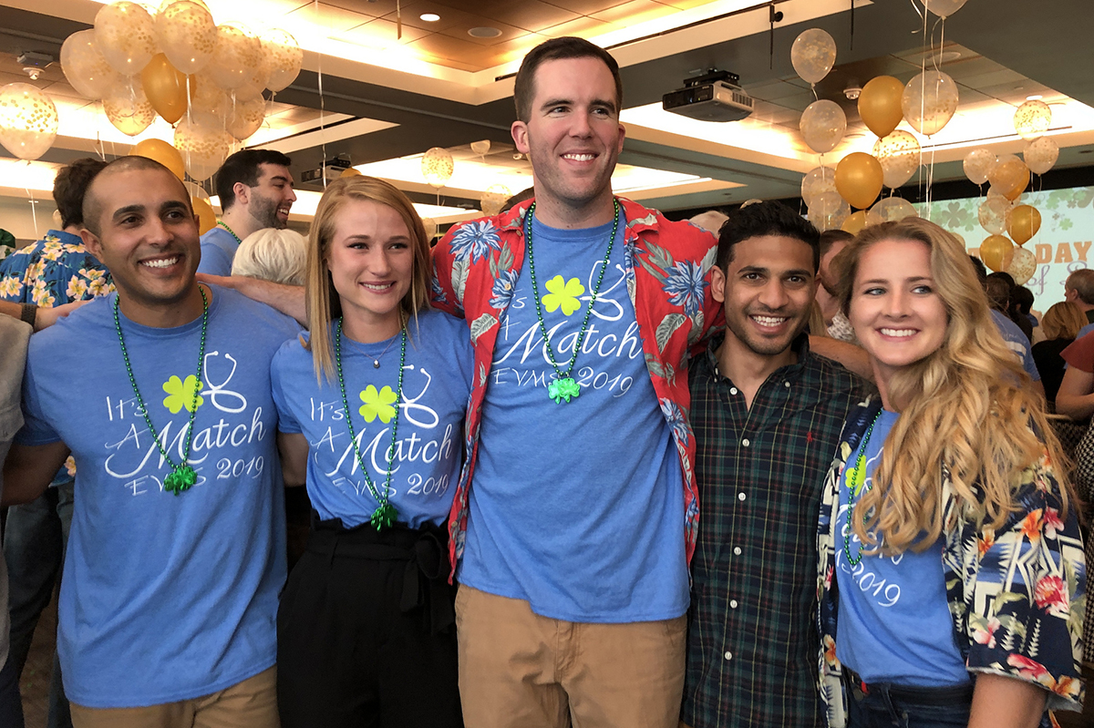 Five fourth-year EVMS medical students celebrate news of their residency plans at Match Day 2019 with balloons in the background.