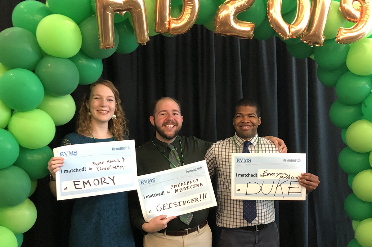 Three fourth-year EVMS medical students hold signs listing their 2019 Match Day results with green balloons overhead.