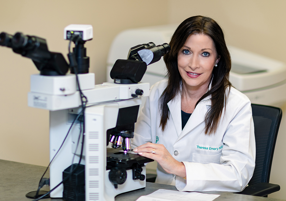 Theresa Emory, MD working at a microscope.