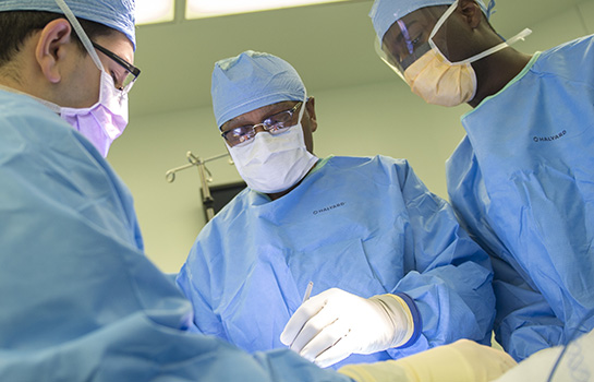 L.D. Britt, MD performing surgery in blue scrubs