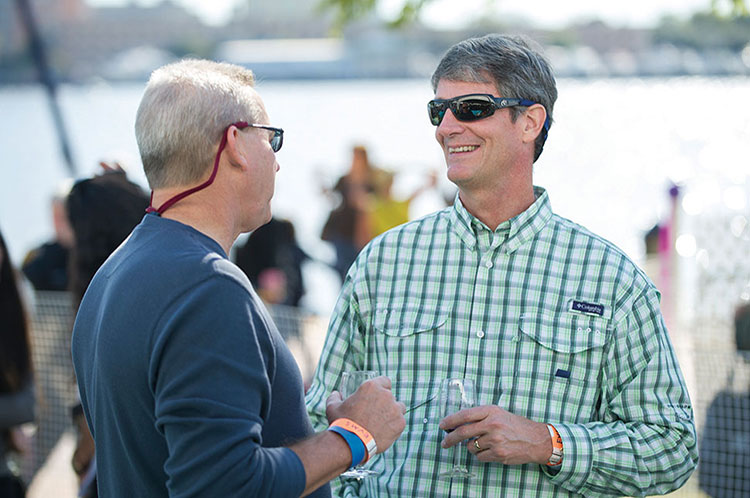 Todd Palmerton MD (MD '85), and F. Taylor Wootton III, MD (MD '85) caught up with each other during Alumni Weekend at the EVMS Alumni Chalet at the Town Point Virginia Wine Festival.