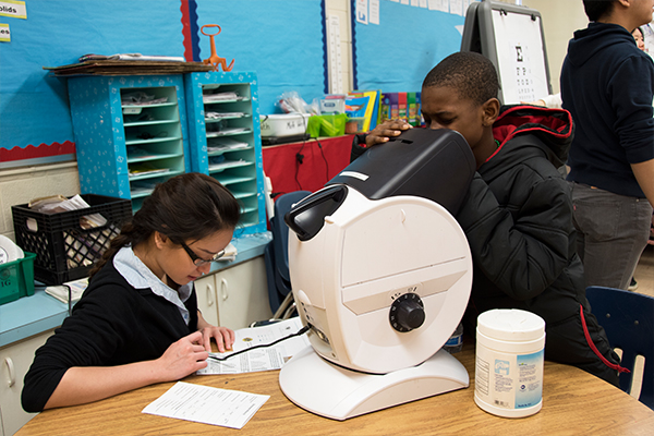 Elementary students using a machine to test their vision.