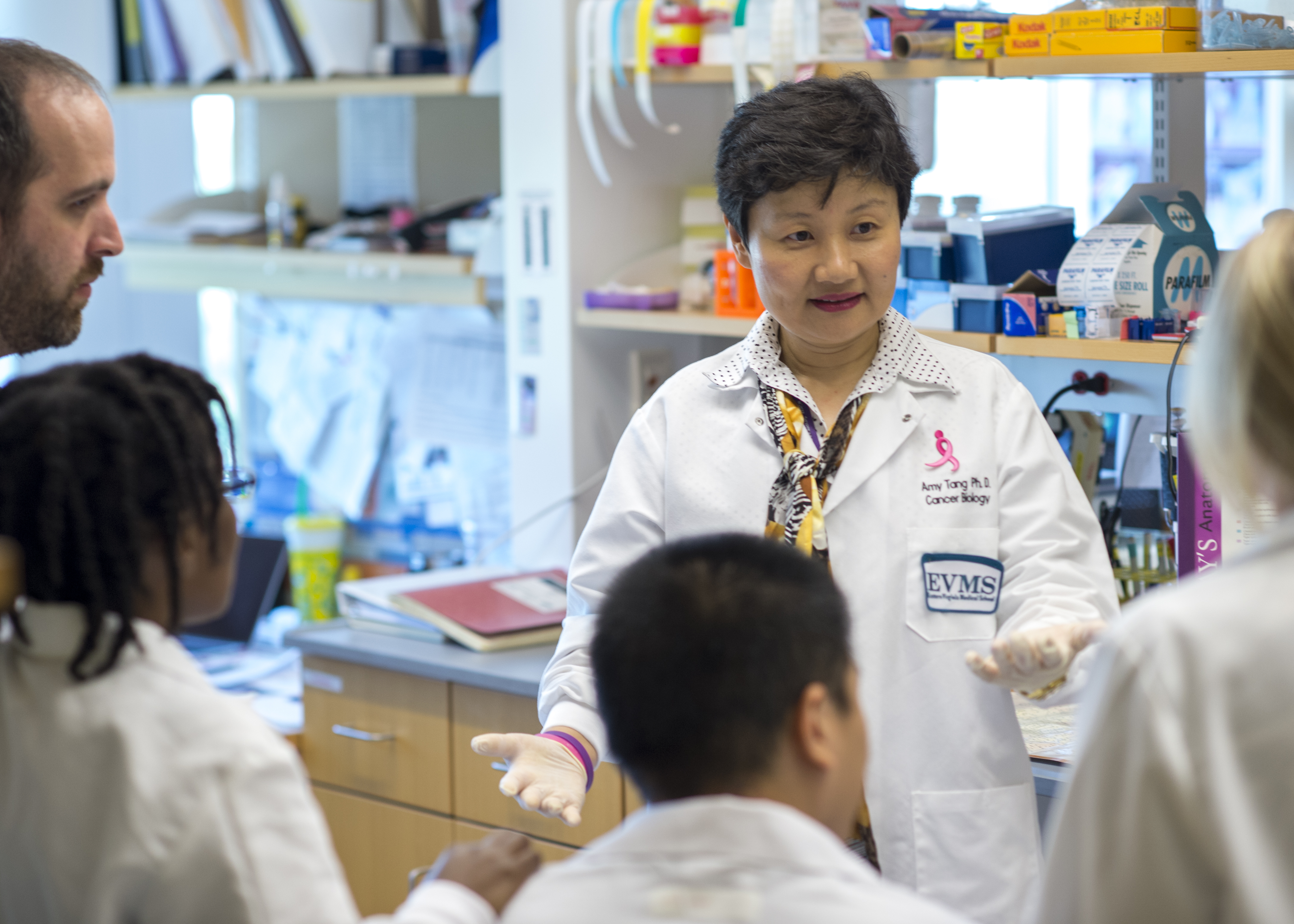 Dr. Tang stands with her research assistants in her lab as shw instructs them.