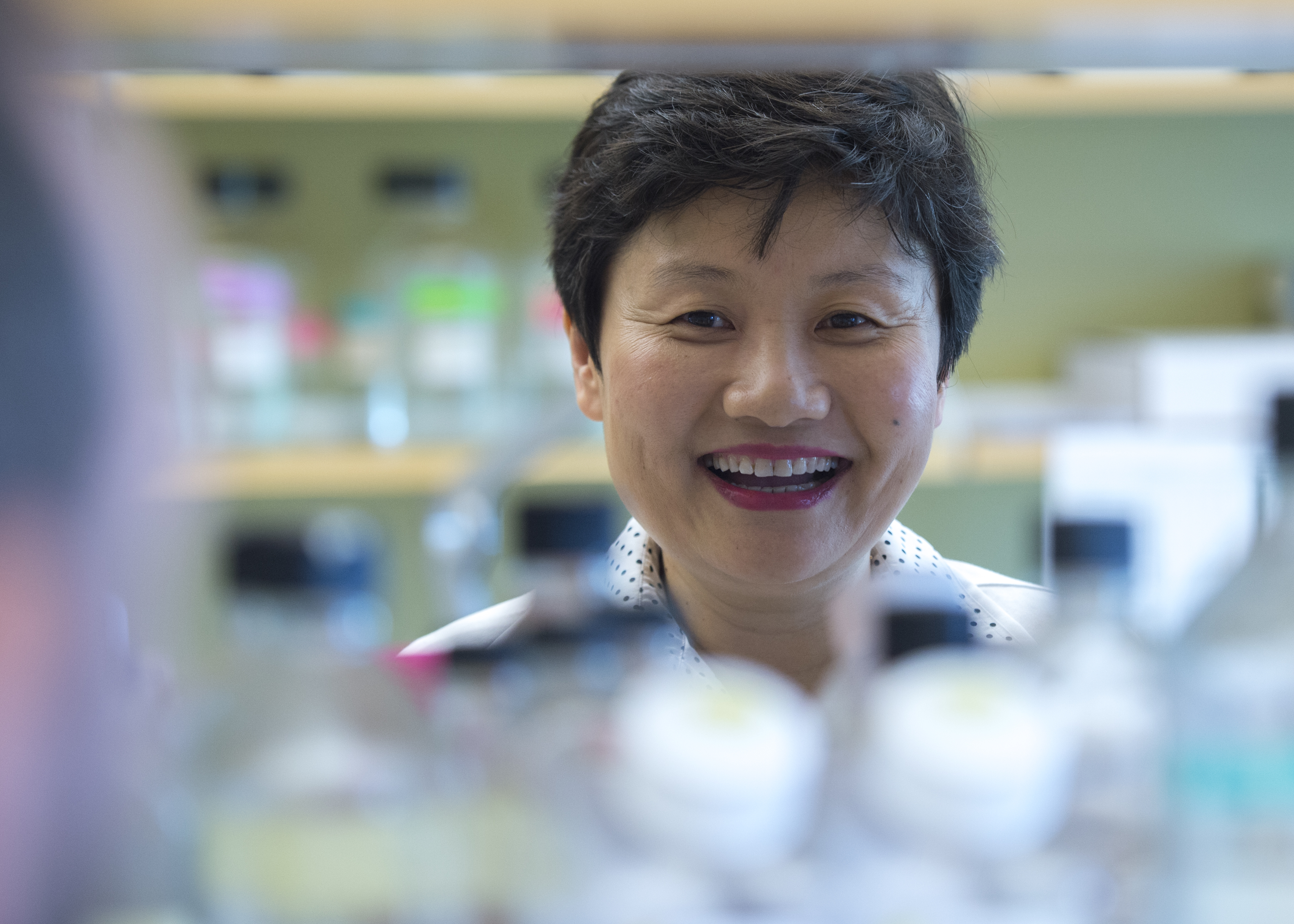 Amy Tang, PhD smiles beautifully through a lab bench as she watches her students learn by doing.