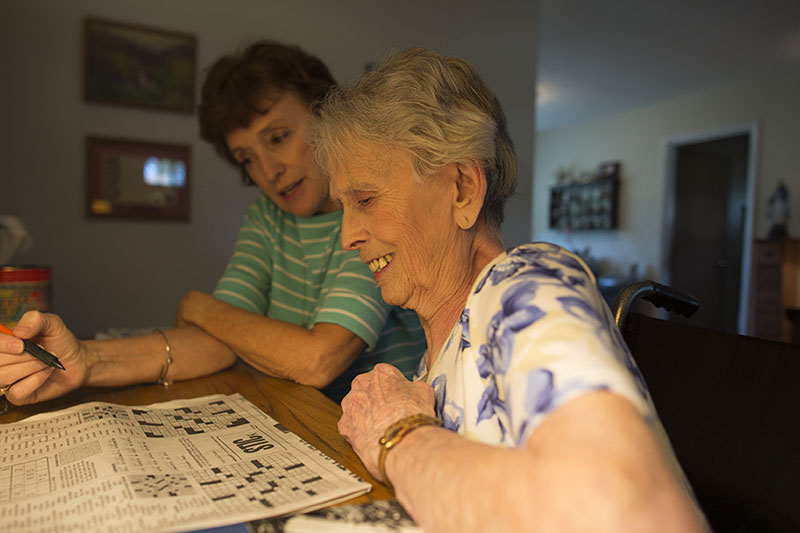 Kathy O'Hara looks on as Kathleen works a crowssword puzzle.