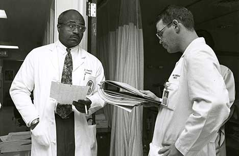 A vintage shot of Dr. Britt discussing charts with a fellow physician