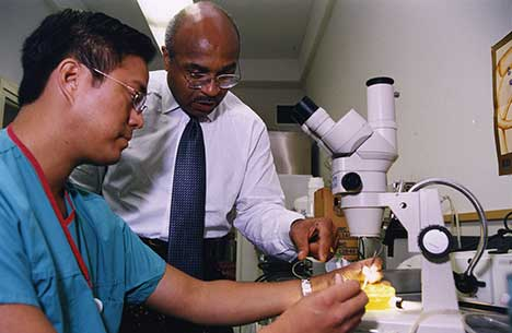 A colorized image of Dr. Britt assisting a student with using a microscope