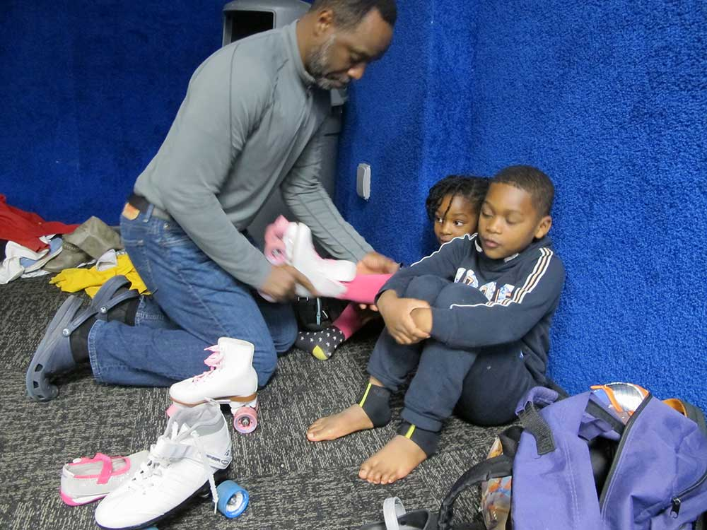 Dr. Salkey's husbands helps their children take off their skates.